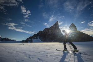 A Climber Skis across the Wind Blown Ice Cap of the Wohlthat Mountains by Keith Ladzinski