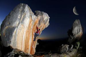 A Man Climbs a Rock in the Cederberg Wilderness Area, under a Moon by Keith Ladzinski