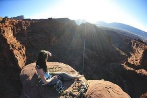 A Woman Relaxes after Climbing to the Top of a Desert Spire by Keith Ladzinski