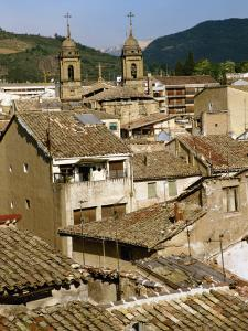 Old Buildings with Tiled Roofs and a Church Behind at Estella on the Camino in Navarre, Spain by Ken Gillham