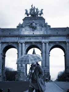 Belgium, Brussels; a Girl Walking with an Umbrella in Front of the Arc Du Triomphe by Ken Sciclina