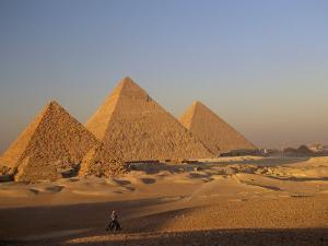 A Man on a Donkey in the Desert Near the Great Pyramids of Giza by Kenneth Garrett