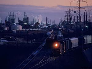 Trains Surrounded by Industrial Plants by Kenneth Garrett