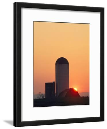 Twilight View of a Barn and Silo Silhouetted against the Sun