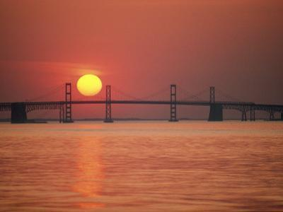 View from the Water of the Chesapeake Bay Bridge and the Setting Sun by Kenneth Garrett