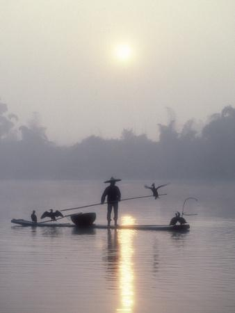 A Fisherman Uses His Cormorants to Catch Fish in the Early Morning