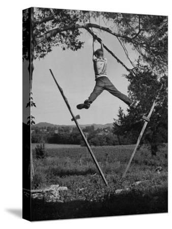 Kenneth Merriman Swinging on Tree Limb after Kicking Away Stilts