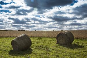 Hay Bales and a Corn Field under a Cloud-Filled Early Autumn Sky by Kent Kobersteen