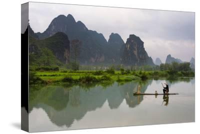 Fisherman on bamboo raft on Mingshi River at sunset, Mingshi, Guangxi Province, China