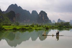 Fisherman on bamboo raft on Mingshi River at sunset, Mingshi, Guangxi Province, China by Keren Su