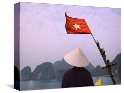Girl with Conical Hat on a Junk Boat with National Flag and Karst Islands in Halong Bay, Vietnam