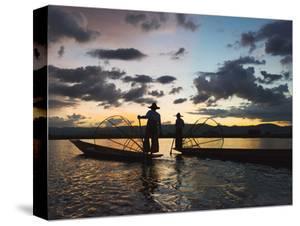 Intha fisherman rowing boat with leg at sunset on Inle Lake, Shan State, Myanmar by Keren Su