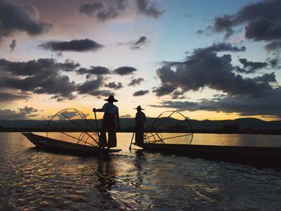 Intha fisherman rowing boat with leg at sunset on Inle Lake, Shan State, Myanmar