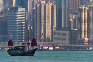 Junk boat and high-rise in Victoria Bay, Hong Kong, China by Keren Su
