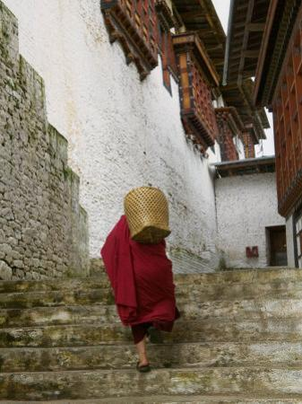 Monk Carrying Basket in Trongsa Dzong, Bhutan by Keren Su