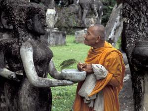 Old Monk Praying at Xieng Khuan (Buddha Park), Laos by Keren Su