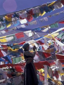 Pilgrim Praying Among Flags, Tibet by Keren Su