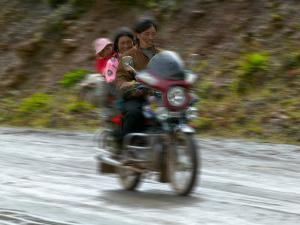 Tibetan Family Traveling on Motorbike in the Mountains, East Himalayas, Tibet, China by Keren Su