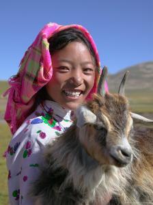 Tibetan Girl Holding Sheep in the Meadow, East Himalayas, Tibet, China by Keren Su