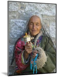 Tibetan Woman Holding Praying Wheel in Sakya Monastery, Tibet, China by Keren Su