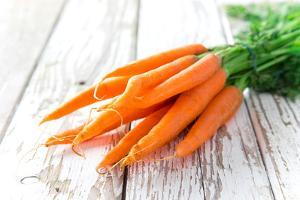 Fresh Carrots on Wooden Background by Kesu01