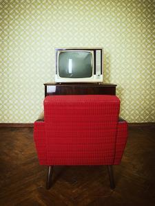 Vintage Room with Two Old Fashioned Armchair and Retro Tv over Obsolete Wallpaper. Toned by khorzhevska