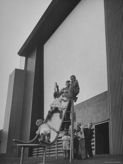 Kids Enjoying Slide in Mini Playground in Front of Rancho Drive-Allan Grant-Photographic Print