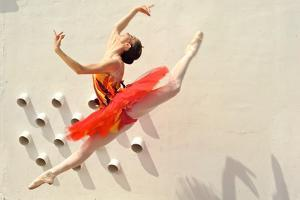 A Ballerina Dancing and Leaping Wearing a Red Dress by Kike Calvo
