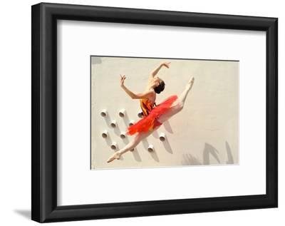 A Ballerina Dancing and Leaping Wearing a Red Dress
