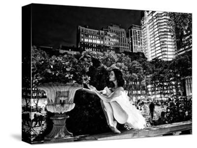 A Ballerina in White Tutu Smelling a Flower in Bryant Park at Night