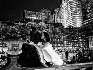 A Ballerina in White Tutu Smelling a Flower in Bryant Park at Night by Kike Calvo