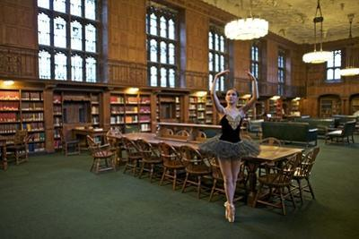 A Classical Ballerina Dances On Pointe In A Library's Reading Room by Kike Calvo