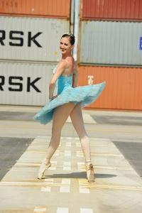A Dancer Of The National Ballet Of Panama, Posing Near Containers by Kike Calvo