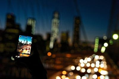 A Man Taking Photos of Downtown Manhattan at Night Using His Cell Phone by Kike Calvo