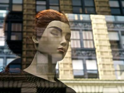 A Mannequin and Buildings Reflected in a Soho Store Window