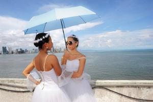 Dancers Talking Under A Blue Umbrella, With Panamas Skyline Behind by Kike Calvo