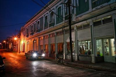 Headlights Shine From a Car Parked on a Deserted Street in Cienfuegos by Kike Calvo