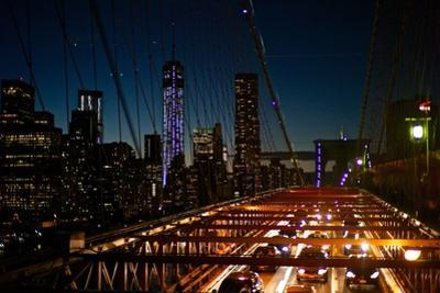 Traffic on the Brooklyn Bridge at Night with a View of Manhattan Skyscrapers by Kike Calvo
