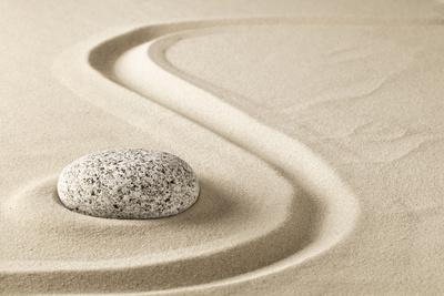 Zen Meditation Stone in Sand. Concept for Purity Harmony and Spirituality. Spa Wellness and Yoga Ba