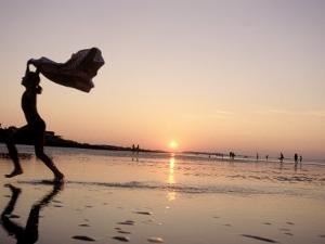 Silhouetted Girl Runs with Beach Towel, MA by Kindra Clineff