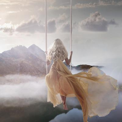 Attractive Woman Sitting on the Swing Above the Calm Lake