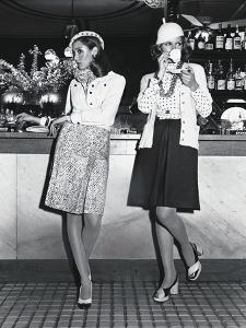 Two Models Standing at a Bar Counter, Smoking and Drinking Coffee by Kourken Pakchanian