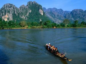 Longboat Crossing Nam Song from Limestone Formations with Honeycomb Caves, Vang Vieng, Laos by Kraig Lieb