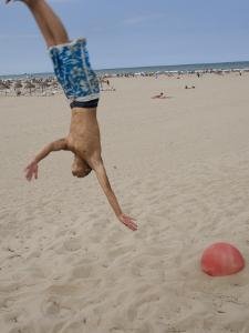Boys Jumping at Las Arenas Beach by Krzysztof Dydynski