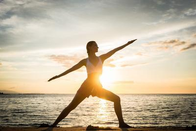 Full Length Side View of the Silhouette of a Fit Woman Practicing the Warrior Yoga Pose against Sky