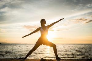 Full Length Side View of the Silhouette of a Fit Woman Practicing the Warrior Yoga Pose against Sky by Kzenon