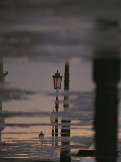 Lampposts Reflected on Wet Pavement after a Rain-Raul Touzon-Photographic Print