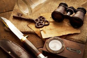 Treasure Hunting Setting, A Compass, Binoculars, Knife and a Old Key on a Old Wooden Desk by landio