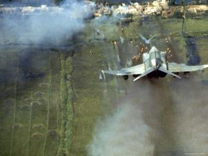 American F4C Phantom Jet Firing Rockets into Viet Cong Stronghold village During the Vietnam War by Larry Burrows