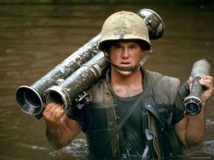 American Marine Pfc. Phillip Wilson Carrying Bazooka Across Stream Near DMZ During Vietnam War by Larry Burrows